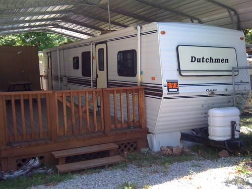 1996 Dutchmen 36' with slide on lot with deck