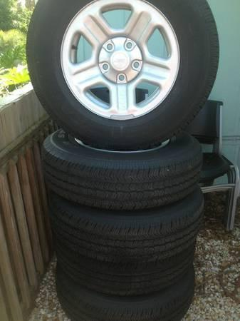 set of 5 Goodyear wrangler tires and stock jeep rims -