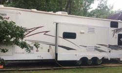 2006 Forest River All American Sport SPORT 385RLTS 5th Wheel Toy Hauler Offering a spacious layout, 3 slides, new hardwood flooring installed in living area, two recently replaced ac units (15000BTU l