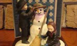 """Amish Heritage """"A Winter Holiday"""" features an Amish boy and girl building a snowperson together. The detailed snowperson includes a decorated straw hat, scarf, carrot nose, coal eyes, mouth and button"""
