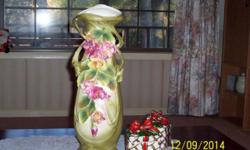 """Antique 19"""" vase with pink and yellow flowers, green leaves on a green and cream colored background. Bottom has """"AUSTRIA"""" 8448. Made between 1900 and 1905-by the AMPHORA PORCELAIN WORKS. (1892-1945)."""