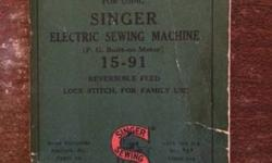 Singer sewing machine built into a very nice table with drawers and sitting stool. Original instructions, extra feet and needles also come with!