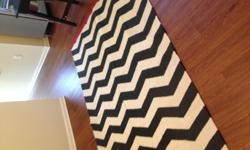 5x8 area rug, 100% cotton, hand made. Feels more like wool than cotton. Great condition.Black and cream chevron stripes with red on each end.