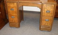 Beautiful art deco desk which could also be used as a dressing table or vanity. Excellent detailing on the front in classic art deco style. Two tone wood grain. This classic piece is on small casters