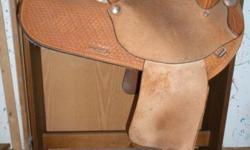 Used - Natural Color Barrel Racing Saddle Minimal wear, suede seat, plain (rough) fenders, basket weave pommel and skirt, horn and stirrups are covered, stamped silver trim, cantle height is approxima