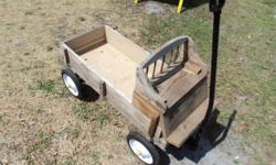 This custom made wagon looks like an old fashioned traveling wagon from when settlers traveled across the County with all their belongings. It is the size of a regular child's wagon, with a seat and c