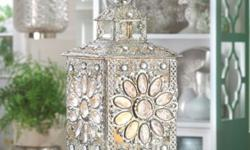 Live like royalty! Enjoy the sparkle of all the riches in the kingdom that are gathered in this stunning tabletop candle lantern. Faceted jewels set inside luxurious silver-tone filigree dazzle when a