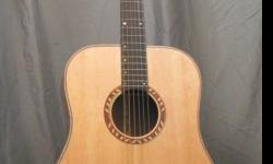 """This is a one of a kind guitar.  Highly figured Canadian Bearclaw Sitka Spruce Top  Ancient Kauri with """"White Bait on Waves"""" figure back and sides  David Freeman's signature flame maple binding  Custo"""