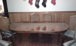 Solid wood table with two removable leafs. Six chairs, two are captain chairs. The table has some wear, such as all the chairs could use new seats/upholstery. The top of the table shows signs of a too