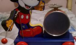 For sale is a 60th Anniversary reproduction Fisher-Price Mickey Mouse Pull Toy. As you pull him by his cord, he beats the drum with his right hand and plays the cymbals with his left hand. Has never b