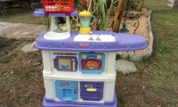 Fisher Price Kitchen Fun kitchen with a sink, stove top, oven, refridgerator, and storage cabinet. Includes a blender, some food, utensils, and a shopping basket to carry around. --------------- Come
