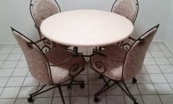 A kitchen or dining room furniture set. A 42-inch wide hard composite table with a stone-like finish, and 4 chairs on wheels.