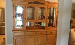 Lovely Oak Cabinet with 18' pull out side server/boards. Honey Oak in color. Base has adjustable rack. 4 drawers in base. Mirrored backing in hutch. Open middle location. Hutch has 2 glass shelving ti