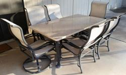 7-piece patio furniture set, with granite table, 2 spinning chairs and 4 standard chairs. All chairs have just had brand new fabric slings installed. The stone table is in excellent shape.