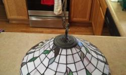 This Tiffany Style Hanging Lamp is 18 inches in diameter, about 12 inches high and can hang two feet from the ceiling (adjustable). It is in great condition and takes a 100 Watt light bulb. Asking $125.00.