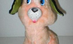 """This vintage pink stuffed dog has a rubber nose and mouth, big bright plastic eyes, and black furry floppy ears. He is wearing a mint green cap with blue brim. He sits 12"""" tall. Has no tags. He is in"""