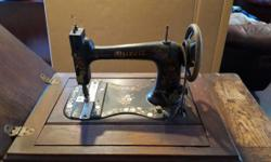 Vintage sewing machine in cabinet; I inherited it and don't know if it works, but you can come by and try it! Otherwise it looks great as a unique decorative piece or even a side table. Check out the