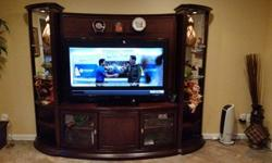 """Selling a beautiful 3 piece wall system. Big enough to hold up to a 60"""" tv. The side systems have one-touch lighting, mirrored backglass and racks. The center unit has 2 glass door cabinets with shelv"""