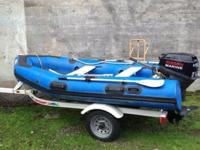 Achilles inflatable boat with outboard motor. Dinghy is