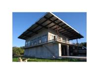 Concrete, open designed home set on a hill top with