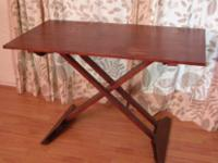 Dark solid wood table with scissor style folding legs.