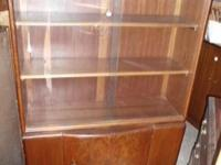 It has glass doors at the top with 2 shelves. The