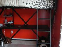 A black and gray metal loft bed with desk
