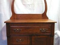 1870's solid oak wash stand has a towel holder harp in