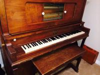This vintage brown mahogany and walnut piano is selling