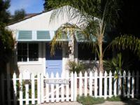 Charming beach style cottage set behind palms on a