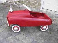 This is a 1957 Murray Fire Chief pedal car. It has