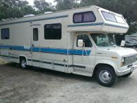 This 1989 Class C RV is a bed over cab and rear bedroom