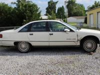 White Chevy Caprice Classic. Big car, has some body
