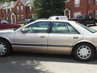 Champagne color 1997 Cadillac SLS w/ approximately