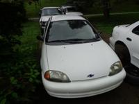 THIS 1999 CHEVY METRO LSI SEDAN IN WHITE HAS GREY CLOTH