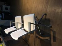 Two white leather swivel chairs in good condition.