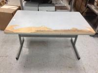 2 well utilized tables/desks, tops are rough yet the
