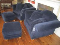 Two dark blue overstuffed chairs with ottomans and two