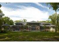 Beautifully sited on five private acres, this custom