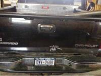 Black tailgate for sale, has a dent in it, does not