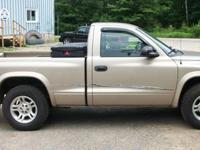 2003 Dodge Dakota pickup. Truck is gold with black