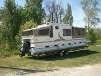 32' Tracker Party Cruiser with cabin sitting on Green