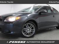 This Scion TC Coupe has a Black Sand Pearl exterior and