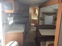 Travel trailer sleeps 8, with slide out dining area.