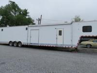 It is a white 50-ft car hauler with living quarters in