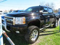 It is a lifted Z71 four door that is black and has