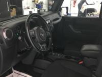 This 2016 Jeep Wrangler Unlimited Sport in granite
