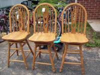 WE HAVE FOR SALE A SET OF 3 OAK SWIVEL BAR TYPE CHAIRS