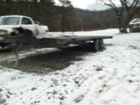 12,000 lbs GVW flatbed trailer with ramps. the bed is