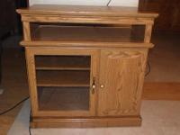 USED OAK TV STAND AND DVD, CD STORAGE CENTER. HAS TOP